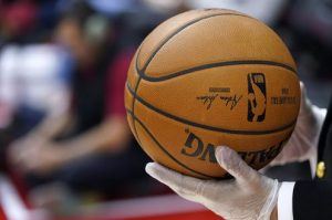 A security guard wears gloves while holding a basketball during halftime of an NBA game in Houston on March 5, 2020. The NBA has told players to avoid high-fiving fans and to avoid taking any item for autographs. AP Photo/David J. Phillip